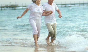 זוג מבוגרים בים אחרי טיפול במחלות זקנה